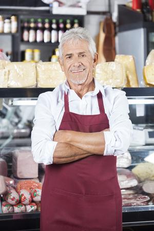 Retrato, confiado, mayor, vendedor, posición, brazos, cruzado, tienda de comestibles