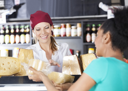 Happy saleswoman assisting young customer in buying cheese at grocery store
