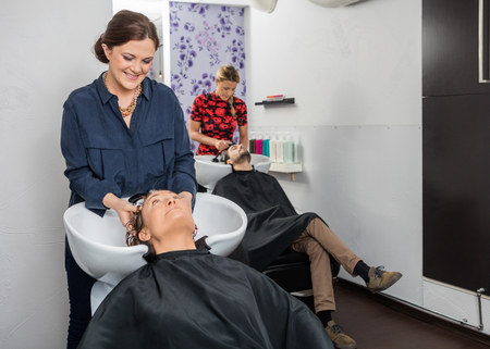Female hairstylists washing customers hair at beauty salon