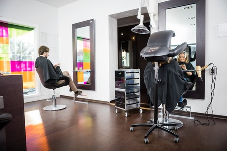 beauty parlor: Male and female customers undergoing hair treatment in beauty salon