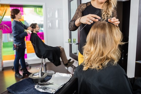 beauty parlor: Female hairstylist working on customers hair in beauty parlor Stock Photo