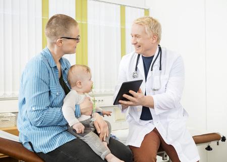 niños sentados: Feliz médico maduro mostrando tabletas digitales a la mujer con el bebé en el hospital