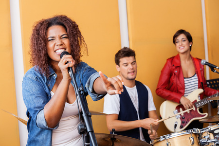 musical band: Passionate female singer pointing while performing in recording studio