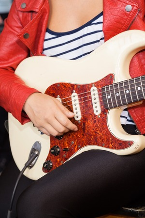midsection: Midsection of woman playing electric guitar in recording studio Stock Photo
