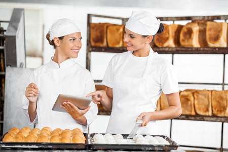 panino: Smiling female Bakers using digital tablet while looking at each other in bakery