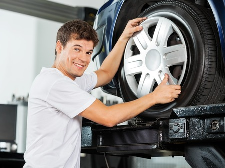 hubcap: Side view portrait of happy male mechanic fixing hubcap to car tire at garage Stock Photo