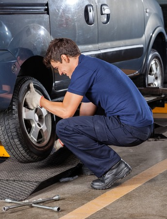 replacing: Side view of male mechanic replacing car tire at garage