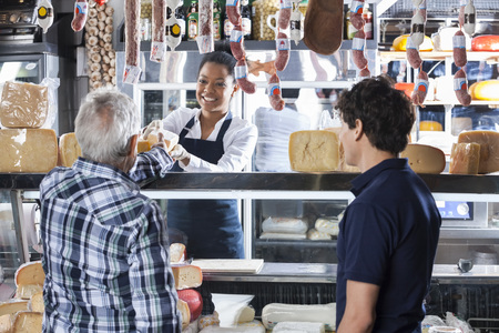 Happy young saleswoman selling cheese to customers at shop