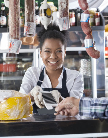 accepting: Portrait of happy saleswoman accepting credit card payment from customer in cheese shop