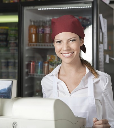 checkout counter: Portrait of happy young saleswoman at checkout counter in grocery store Stock Photo