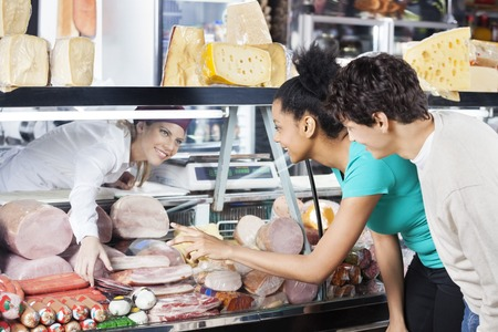 meat counter: Young couple selecting product from display cabinet while saleswoman assisting them in grocery store Stock Photo