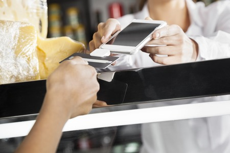 accepting: Saleswoman accepting payment from customer through credit card in grocery store