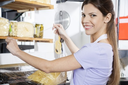 saleswoman: Portrait of smiling saleswoman packing cheese at grocery store