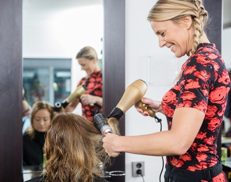blow dryer: Friendly hairdresser styling female customers hair with blow dryer and brush in salon Stock Photo