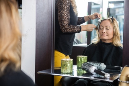 hairtician: Mature woman getting her new hairstyle by beautician in parlor Stock Photo