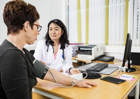 mid adult   female: Mid adult female doctor looking at patient while examining her blood pressure in clinic Stock Photo