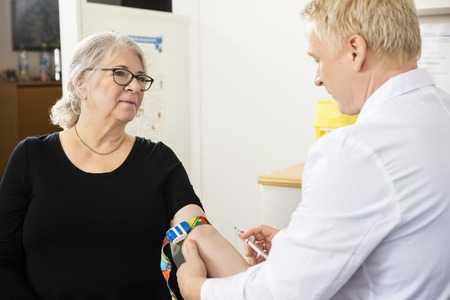 phlebotomist: Senior female patient looking at male doctor collecting blood in syringe Stock Photo