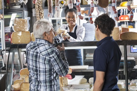 speciality: Happy young saleswoman selling cheese to male customers at shop Stock Photo