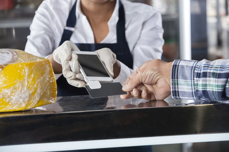 accepting: Cropped image of saleswoman accepting payment from customer in cheese shop