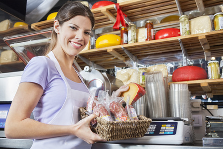 saleswoman: Portrait of confident saleswoman weighing cheese at grocery store Stock Photo