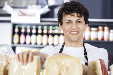 speciality: Portrait of confident salesman arranging cheese in shop Stock Photo
