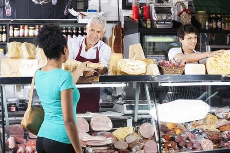 Sorridente venditore senior dando formaggio di cliente femminile al contatore nel negozio di alimentari