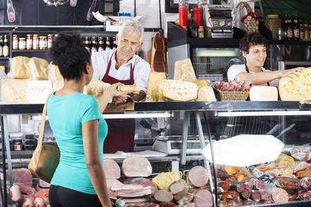 Smiling senior salesman giving cheese to female customer at counter in grocery shop