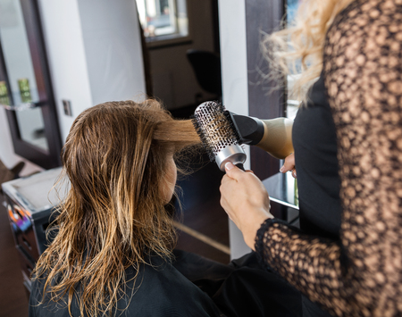 blow dryer: Cropped image of hairdresser styling customers hair with blow dryer and brush in salon