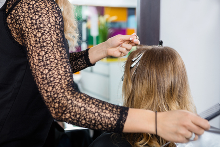 hairtician: Cropped image of hairdresser highlighting female customers hair in salon