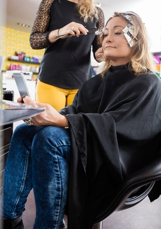 Hairdresser applying hair dye to mature woman in beauty salon