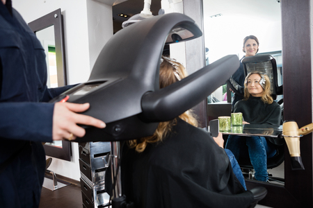 accelerator: Hairdresser adjusting drying accelerator over female customers head in beauty salon