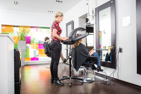accelerator: Hairstylist adjusting drying accelerator over female customers head in parlor