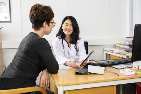 Smiling female doctor showing digital tablet to patient in clinic