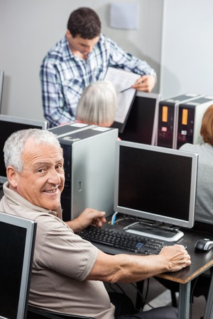 compute: Portrait of happy senior man using compute with tutor and classmates in background at classroom
