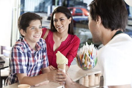 receiving: Smiling mother looking at son receiving vanilla ice cream from waiter in parlor