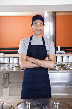parlor: Portrait of confident waiter standing arms crossed at counter in ice cream parlor