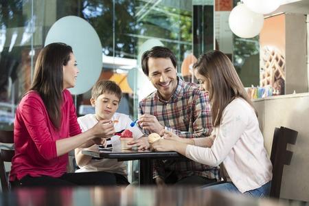 Happy family ayant des glaces alors qu'il était assis à table dans le salon