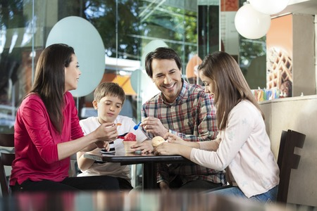 woman with ice cream: Happy family having ice creams while sitting at table in parlor