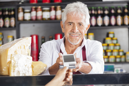 reader: Portrait of senior man accepting payment from customer through credit card in cheese shop