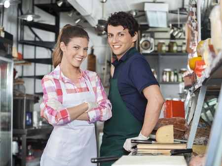 salespeople: Portrait of confident young salespeople at counter in cheese shop