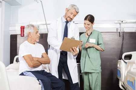 long term care services: Mature male doctor and nurse communicating over report by senior patient in rehab center Stock Photo
