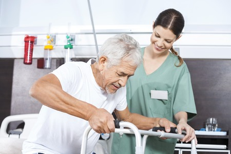 assisted: Happy senior patient being assisted by happy female nurse in using walker at rehab center Stock Photo