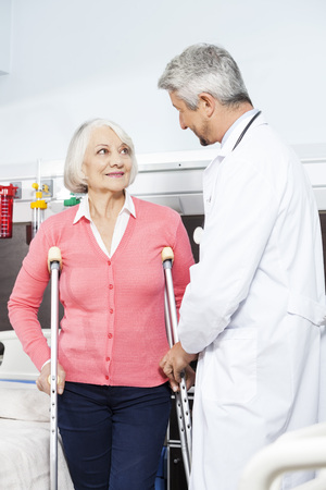 assisted: Smiling senior female patient being assisted by mature doctor with crutches at rehab center