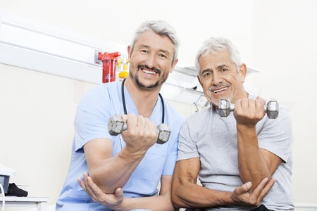 old man happy: Portrait of happy physiotherapist and senior patient lifting dumbbells in rehab center Stock Photo