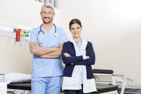 physiotherapists: Portrait of male and female physiotherapists standing arms crossed in rehab center