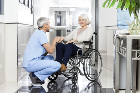 Mature male physiotherapist holding smiling senior woman's hand on wheelchair in rehab center