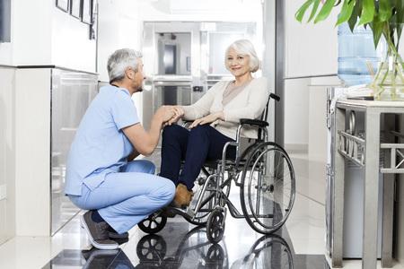 Coppia fisioterapista sesso maschile in possesso sorridente la mano di donna anziano sulla sedia a rotelle nel centro di riabilitazione