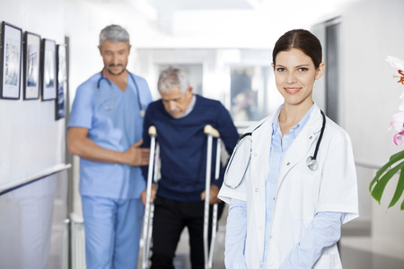 long term care services: Portrait of confident doctor smiling while colleague assisting senior man with crutches in rehab center