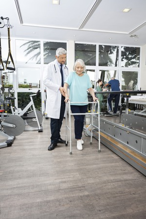 gait: Mature male physiotherapist assisting woman with walker while nurse standing by man exercising in fitness studio of rehab center