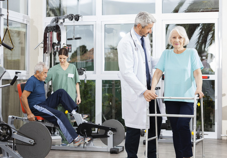 Portrait of senior woman using walker while doctor assisting her at rehab fitness center Foto de archivo